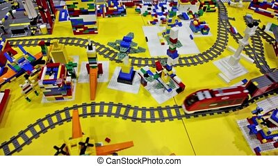 Toy train moves by railroad among different objects