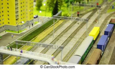 toy train pushes tank wagon on rail in toy modern sity near multistorey apartment block