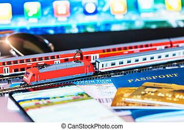 Toy train, tickets, passport and bank card on laptop or notebook