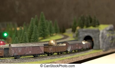 Toy train with smoke moving on model railway.