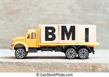 Toy truck hold alphabet letter block in word BMI (abbreviation of body mass index) on wood background