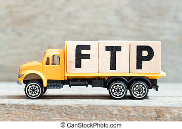 Toy truck hold alphabet letter block in word FTP (Abbreviation of File Transfer Protocol) on wood background