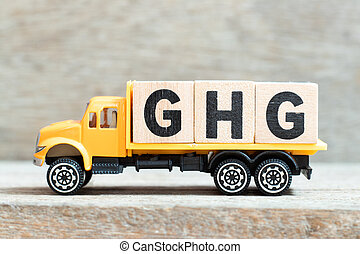 Toy truck hold alphabet letter block in word GHG (greenhouse gas) on wood background