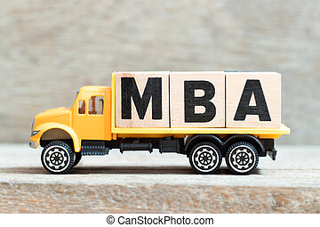 Toy truck hold alphabet letter block in word MBA (Abbreviation of master of business administration) on wood background
