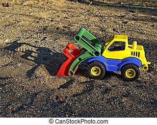 Plastic toy vehicle in sand box at childrens playground.