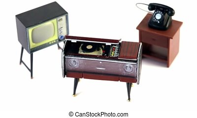 Toy vintage phonograph, phone and tv set circling isolated...