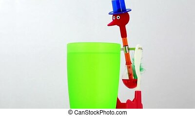 Toy water pendulum in form of bird, liquid fill tube and...