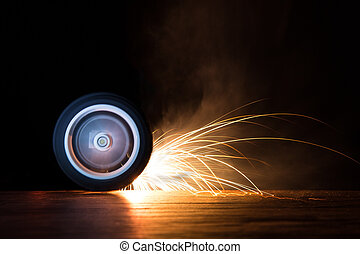 Toy wheel spinning on black background with sparks flying