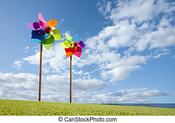 Toy windmill concept of green energy wind farm in field by the sea