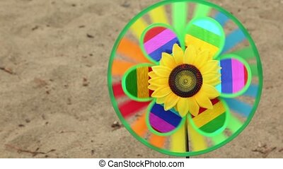 Toy with a sunflower in the center is set in the ground, then the girl took it