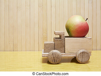 Toy wooden car with red apple