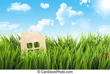 Toy wooden house in green grass on sunshine.