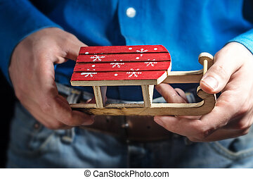 Toy wooden sled and with the hands of a young man. Christmas card. Christmas concept.
