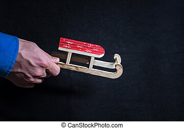 Toy wooden sleigh in the hand of a young man. Christmas card with space for your text. Christmas concept.
