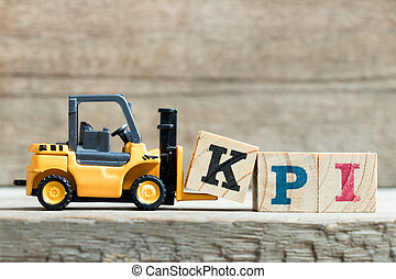 Toy yellow forklift hold letter block K to complete word KPI (Abbreviation of Key performance indicator) on wood background