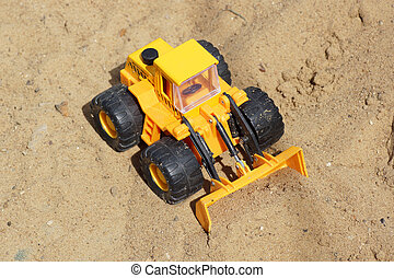 Toy yellow tractor on the sand.