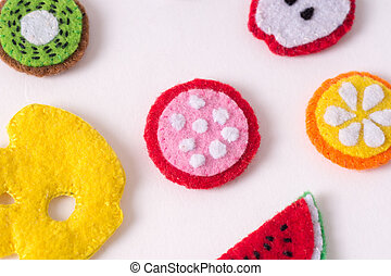 Toys in the form of food and fruits hand made of felt on a white background. Hand sewing