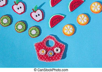 Toys in the form of food and fruits hand made of felt on blue background. Hand sewing