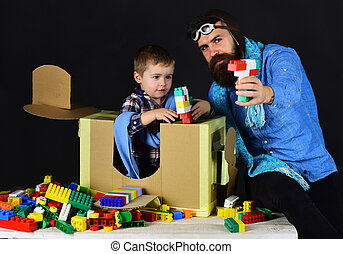 Toys made from constructor for children. Handmade gun for young boy. Father and son play together, black background. Bearded father takes care for little boy. Little boy play with favorite constructor