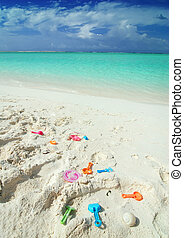 Colorful child toys laying on the beach in the Maldives