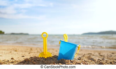 Toys on the sand beach with sea wave select focus shallow...