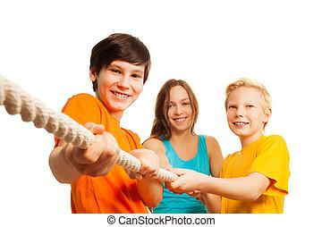 três, adolescente, amigos, puxando, a, corda