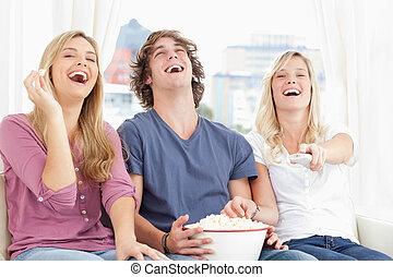 três amigos, comer, pipoca, enquanto, rir, em, a, mostrar