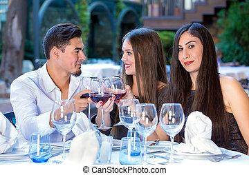 três amigos, tendo jantar, em, um, restaurant.