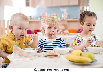 três crianças, comer, de, pratos, em, cuidado dia, centro