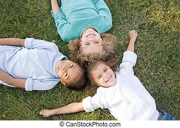três crianças, tendo divertimento
