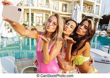 três, encantador, mulheres jovens, em, swimwear, levando, um, selfie