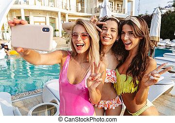 três, excitado, mulheres jovens, em, swimwear, levando, um, selfie