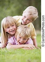 três, filhos jovens, tocando, ao ar livre, sorrindo