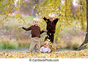 três, filhos jovens, tocando, em, caído sai