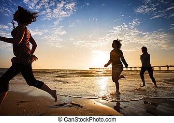 três meninas, executando, por, a, oceânicos, em, pôr do sol