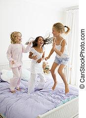 três, meninas jovens, pular, ligado, um, cama, em, seu, pijamas