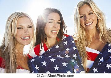 três, mulheres jovens, embrulhado, em, bandeiras americanas, ligado, um, praia