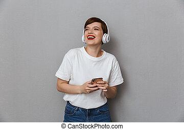 tröttsam, le womanen, ung, mobiltelefon, holdingen, hörlurar, avbild