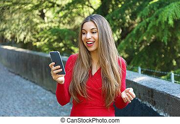 tröttsam, stad, vandrande, kvinna, texting, sweater, parkera, ringa, röd, smart