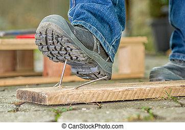 trabajador, con, botas seguridad, pasos, en, un, clavo