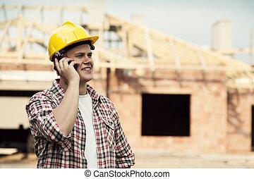 trabajador construcción, con, teléfono móvil