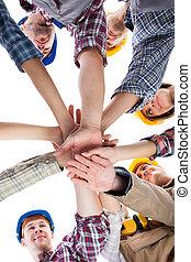 trabalhador construção, empilhando mãos