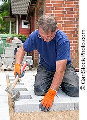 trabalhador, deitando, novo, pedras pavimentando, para, um, pátio