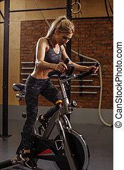 trabalhador, jovem, bonito, menina, fazendo, exercício, ligado, bicicleta, treinamento, aparelho