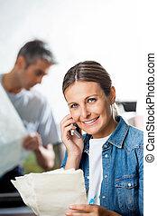trabalhador, segurando, papeis, enquanto, usando, telefone pilha, em, fábrica
