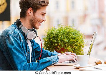 trabalhando, com, pleasure., vista lateral, de, sorrindo, homem jovem, trabalhar, laptop, enquanto, sentando, em, bar calçada