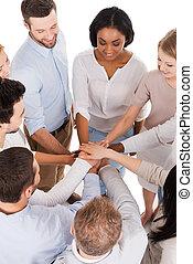 trabalhando, como, um, team., vista superior, de, positivo, diverso, grupo pessoas, em, esperto casual, desgaste, mantendo, seu, mãos apertaram, e, sorrindo, enquanto, ficar, perto, um ao outro