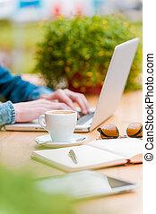 trabalhando, process., close-up, de, homem jovem, trabalhar, laptop, enquanto, sentando, em, bar calçada