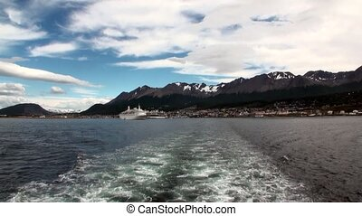 Trace waves on water from ship in port pier of Ushuaia in...