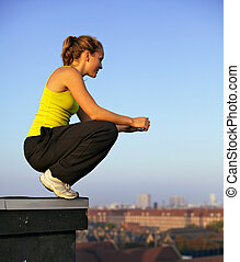 Young female traceur balanced on the very edge of a high urban building preparing herself mentally to participate in parkour.